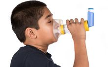 A child users an asthma inhaler.