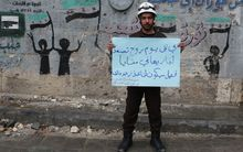In the city of Aleppo, Syrian civil defense team members hold banners as they gather to protest for civilians who starved to death in Madaya.