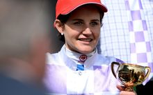 Michelle Payne holding the Melbourne Cup.