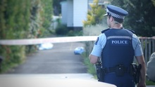 A police officer near the Te Atatu house where Cun Xiu Tian, 69, was found dead.