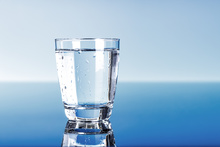 A close-up of a glass of drinking water, on a blue background
