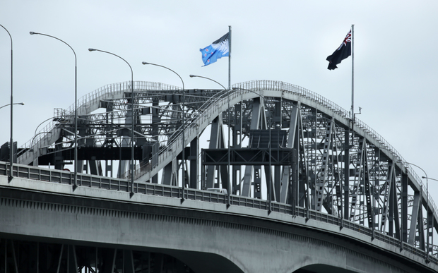 The New Zealand flag flies alongside its challenger on Auckland's Harbour Bridge.