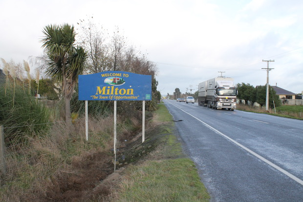 A photo of the road to Milton, showing the town sign and traffic.