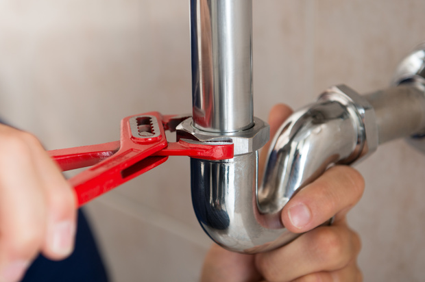 A plumber fixes a pipe with a wrench.