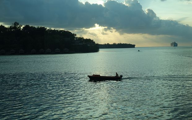 A boat crosses Port Vila habour at sunset.