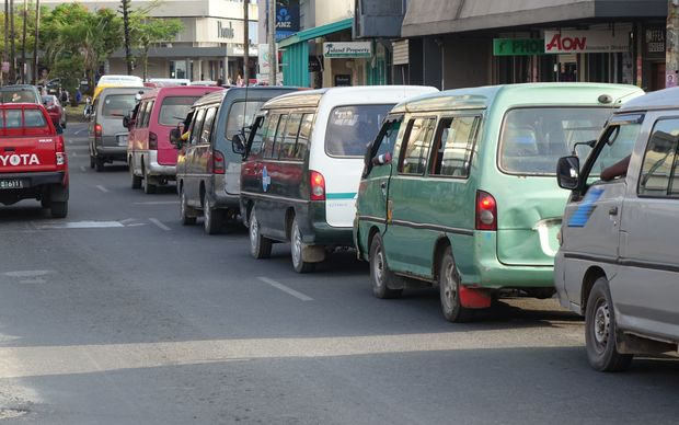 The vans that make up Port Vila's bus service line up along the main street.