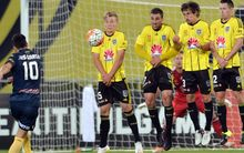 Luis Garcia of the Mariners shooting a free-kick and James McGarry, Manny Muscat, Albert Riera Vidal and Blake Powell of the Phoenix (L-R) reacting.