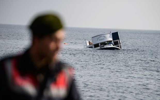 A sinking boat is seen behind a Turkish gendarme off the coast of Turkey.