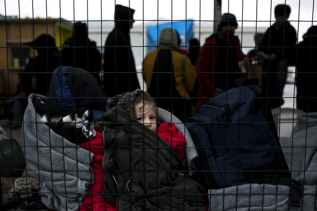 A child waits as people queue inside a migrant registration centre on the Greek island of Samos.