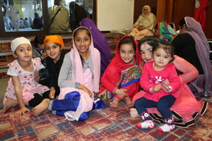Sikh children wait outside the prayer area