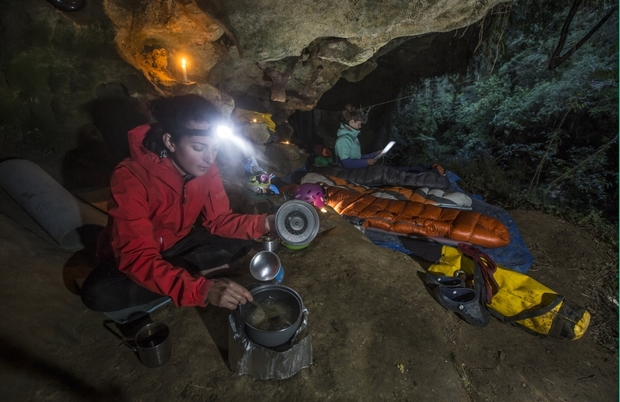 An image showing the cavers preparing dinner at their bivvy underneath a large rock overhang.