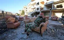 A member of the Syrian pro-government forces sits on a sofa in the strategic town of Salma.