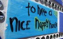 Tile on wall of hope with the words - to have a nice happy house