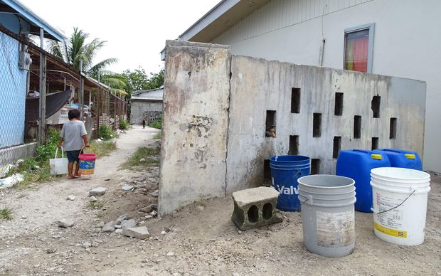 A young Majuro child carries fresh water in buckets to his house.