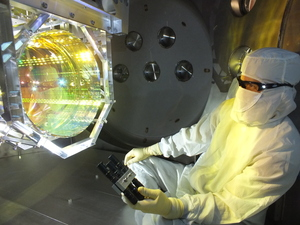 Prior to sealing up the chamber and pumping the vacuum system down, a LIGO optics technician inspects one of mirrors by illuminating its surface with light.