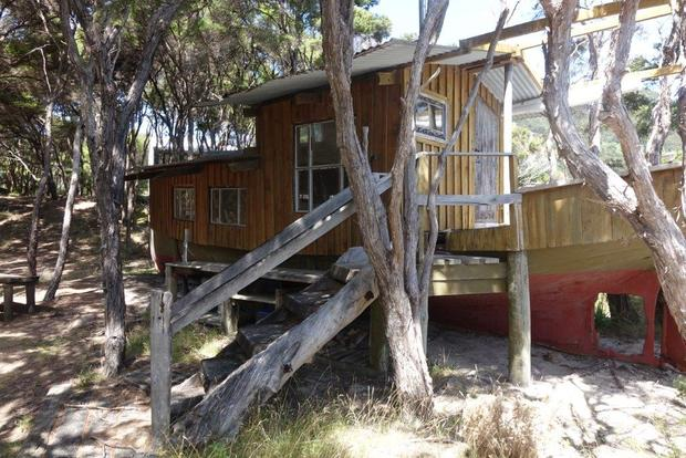 One of three dwellings on the beachfront property for sale at Awaroa is a re-fashioned boat. A crowd funding campaign has raised millions to purchase the land.15 February 2016.