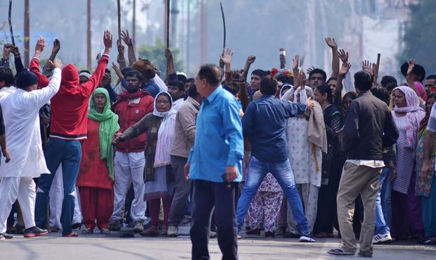 Indian residents gather on a street as others gesture to hold them back amid ongoing caste protests in Rohtak