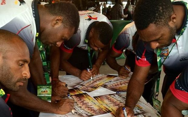 PNG Hunters players sign posters at their 2016 season launch.