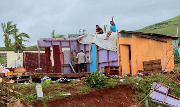 Locals wave from a damaged house in Rakiraki, Fiji, after Cyclone Winston.
