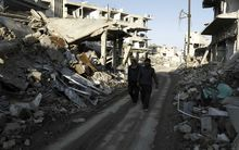 Syrian men walk along a street damaged by shelling in the neighbourhood of Jobar, on the eastern outskirts of the capital Damascus.