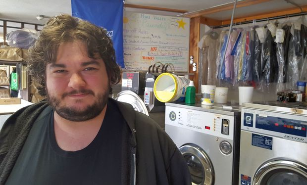 Bearded student stands in front of two big front loader washing machines