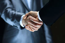 Two men in suits shake hands - close-up (file)