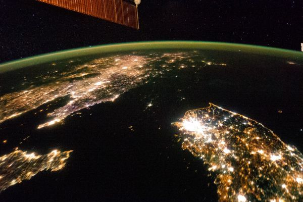 The Korean Peninsula at night. North Korea almost completely dark, the bright spot is Pyongyang.