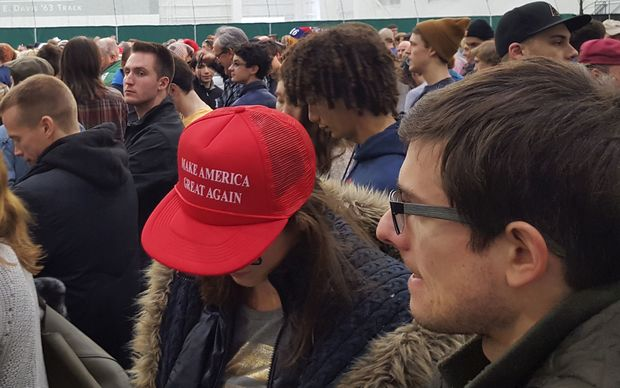 "Girl bows head slightly to show of ""Make America Great Again"" slogan on her red cap"