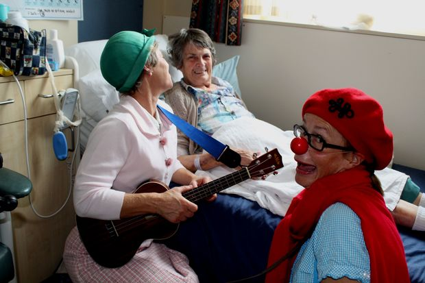 Photo of Clown doctors entertaining Margaret Chelley at Princess Margaret Hospital