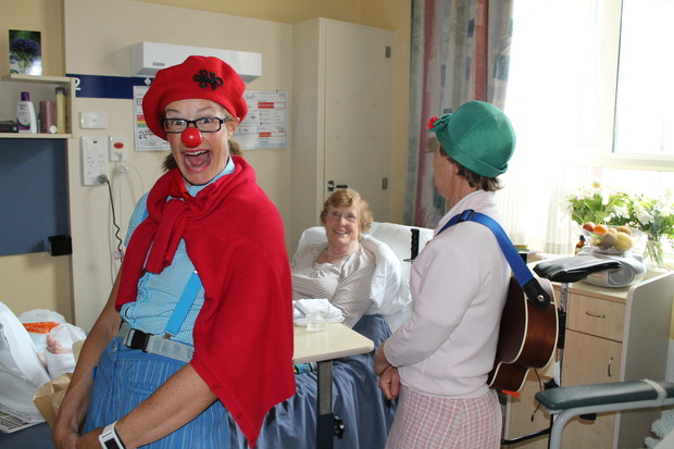 A photo of clown doctors sharing a joke with Phillipa Scott at Princess Margaret Hospital