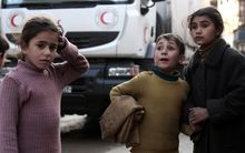 Syrian children meet an aid convoy in a rebel-held suburb on the outskirts of Damascus.