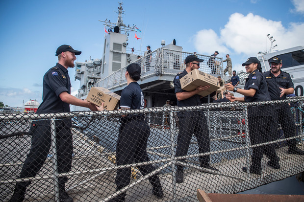 Military personnel offload aid supplies in Fiji.