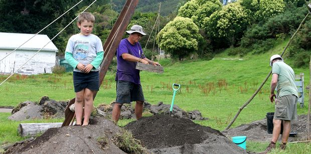 Sieving all the dug-up earth. Local kid Ollie, poses.