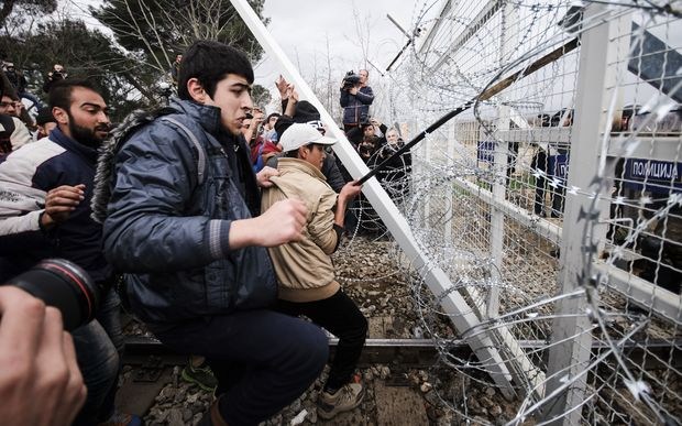 Migrants pushing against a fence at Idomeni in Greece.