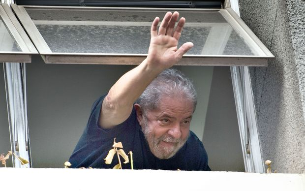 Former Brazilian President Luiz Inacio Lula da Silva waves at supporters from a window of the Workers Party state headquarters in Sao Paulo, on March 4, 2016