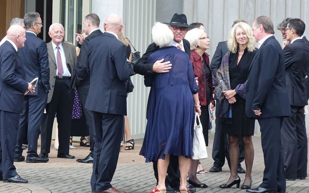 Jeff Crowe (centre) welcomes mourners to the funeral of his brother Martin.