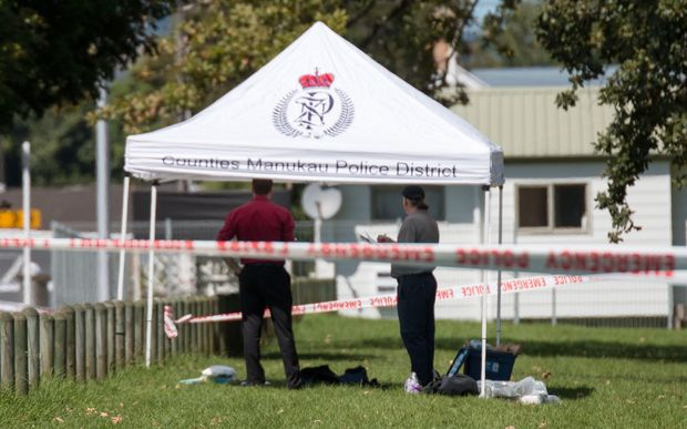 Police gather evidence opposite the train station in Papakura after a shooting early this morning that left one man dead and another seriously injured.