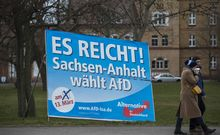 "A couple walks past a campaign poster for right-wing populist Alternative for Germany party reading: ""Enough is enough, Saxony-Anhalt votes for AfD"", in Magdeburg, eastern Germany."