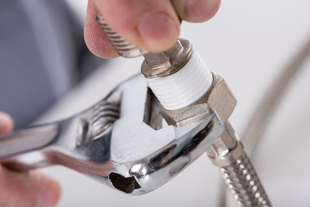 A close-up of a plumber screwing a plumbing fitting onto a pipe