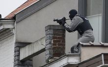 A member of the special forces takes position on a roof near the site of a shooting in the southern Forest district of Brussels on March 15, 2016.