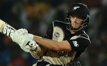 Mitchell Santner sweeps against India at the T20 World Cup.