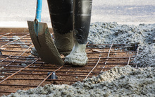 A worker spreads ready-mix concrete over steel mesh (file)