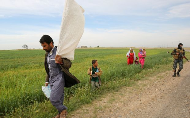 An Iraqi man carries a makeshift white flag as he flees the fighting with his family.