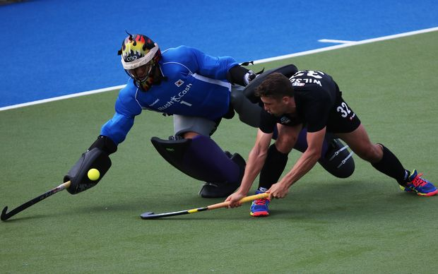 New Zealand's Nick Wilson tangles with Korea's goal keeper.