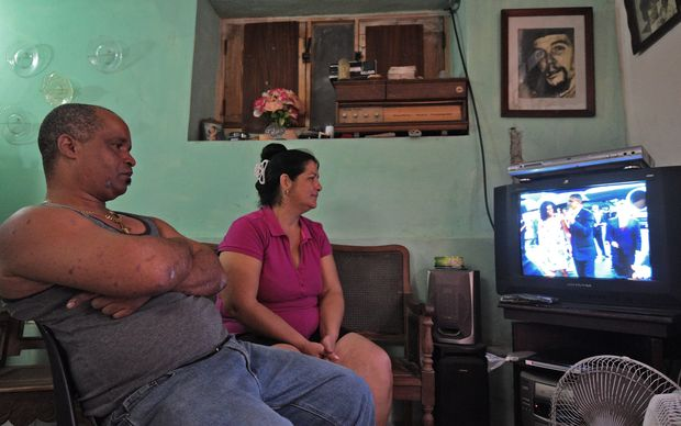 "A Cuban family in Havana, with a photo of legendary Argentine-Cuban revolutionary Ernesto ""Che"" Guevara on the wall, watch on TV the arrival of US President Barack Obama to Cuba on March 20, 2016."