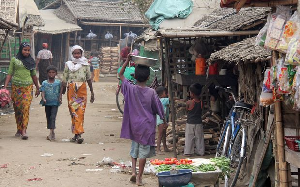 Dusty earth street with pedestrians and makeshift shops