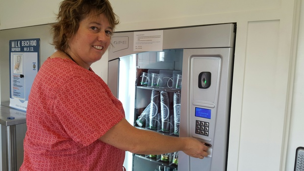 New Plymouth woman Regima Jolly picks up milk from the Beach Road Milk Company vending machine at the farmgate.
