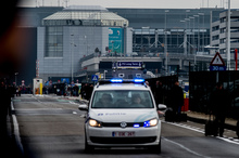 A Belgian police vehicle driving past passengers who are evacuating the Brussels Airport of Zaventem.