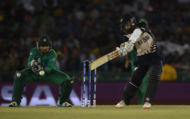 New Zealand's Kane Williamson plays a shot as Pakistan's wicketkeeper Sarfaraz Ahmed looks on during the World T20 cricket match between New Zealand and Pakista