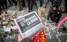 A man holds a flyer reading 'Against terrorism and hate' at a makeshift memorial in front of the stock exchange at the Place de la Bourse (Beursplein) in Brussels